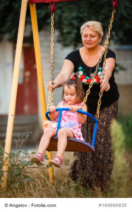 Grandmother pushing granddaughter on swing in park